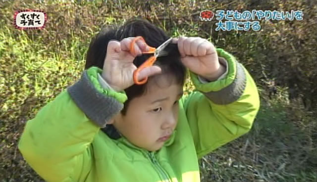 自分で自分の髪の毛を切る男の子