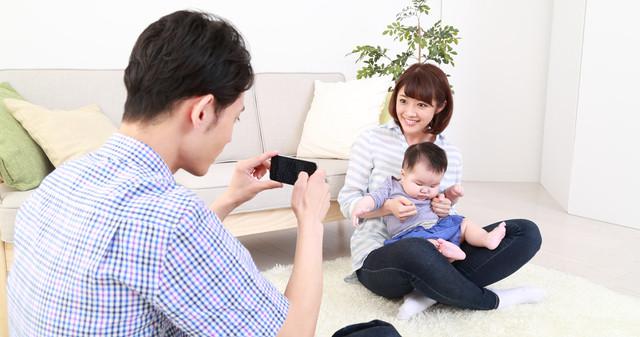 スマホで家族写真を撮るお父さん