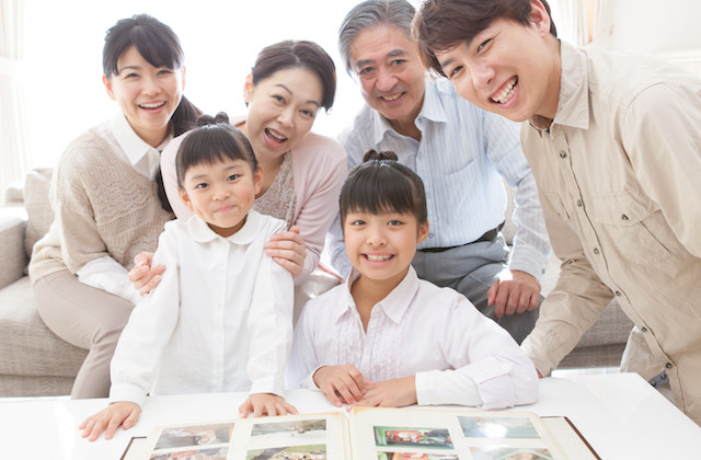 写真アルバムを見て楽しむ家族