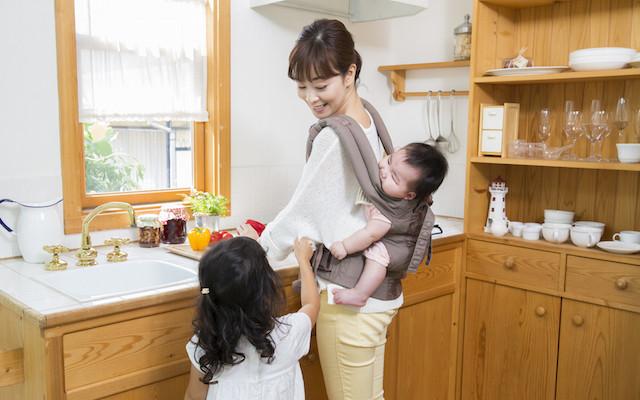 赤ちゃんをおんぶして家事をするお母さん