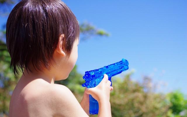 水鉄砲で水遊びする子ども