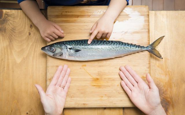 魚を調理する親子