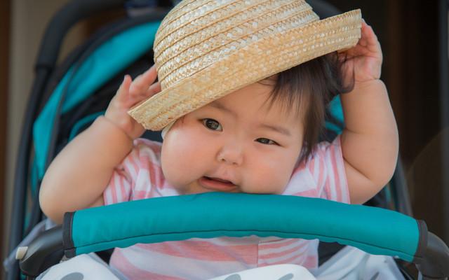帽子をかぶるのを嫌がっている赤ちゃん