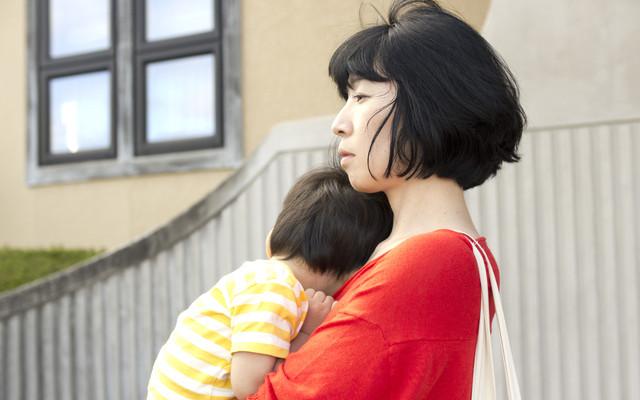 眠る子どもを抱っこする母親