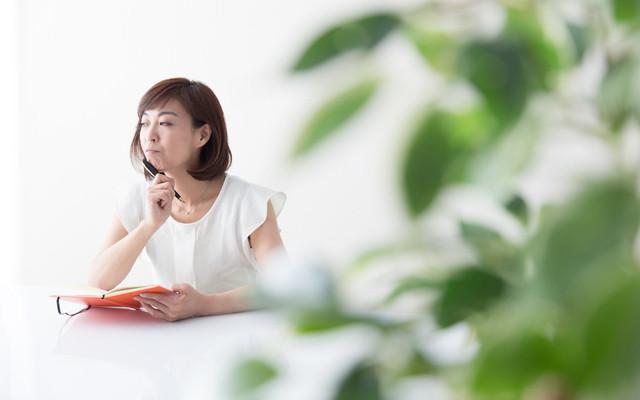 テーブルで手帳を見る女性